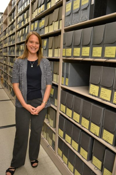 Laura Sullivan, collections archivist at Iowa State University's Parks Library, stands in front of the Carrie Chapman Catt papers.
