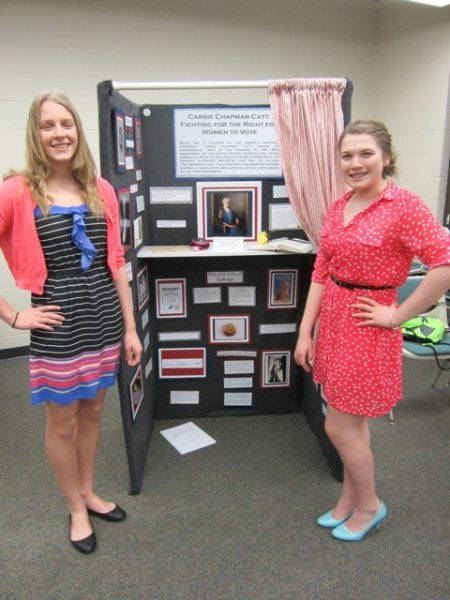 Lexie Higgins and Allison Cotton stand in front of their project at their middle school's History Day.