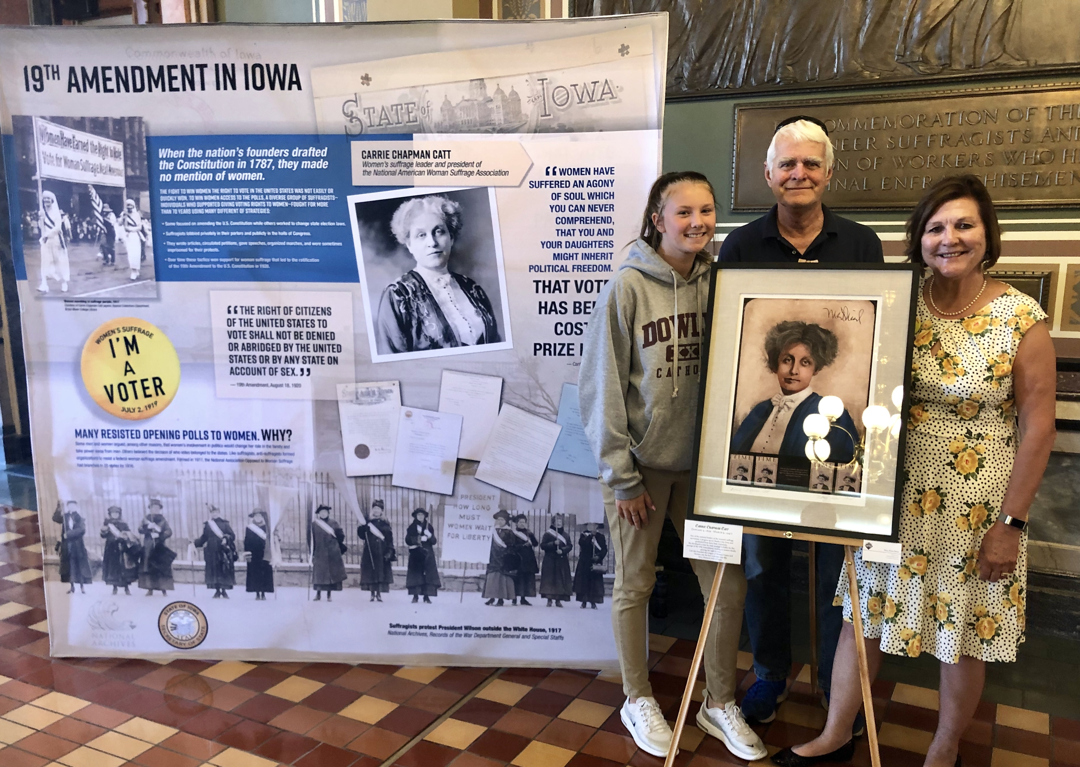 Carrie Lane Chapman Catt's great-great-great-great niece, Margaret Flanagan (left), and Catt's great-great nephew, Tim Lane (middle), pose with Bystrom (right) with Catt's portrait on Sept. 10. at the Iowa State Capitol Building. The portrait is part of the Women's Suffrage Centennial display, where Catt is one of 19 suffragists recognized.