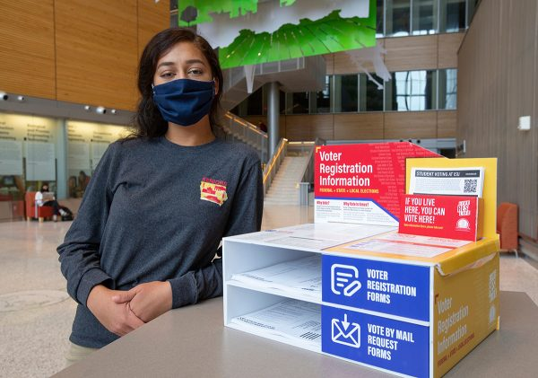 ISU student Sehba Faheem, shown here, and recent graduate Taylor Blair created voter registration literature stands such as this one in the Sukup Atrium in the Biorenewables Research Laboratory. Photo by Christopher Gannon/Iowa State University.